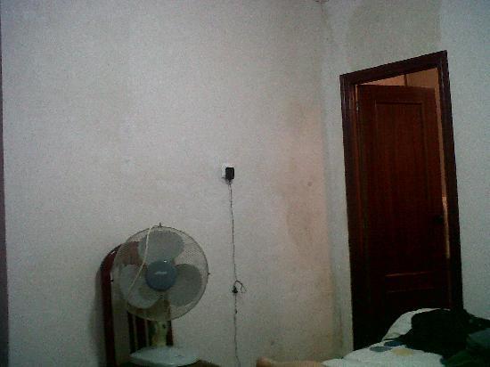 Pensión los Arcos: La habitación. Pared húmeda y nuestro maravilloso ventilador. La puerta que se ve es la del baño