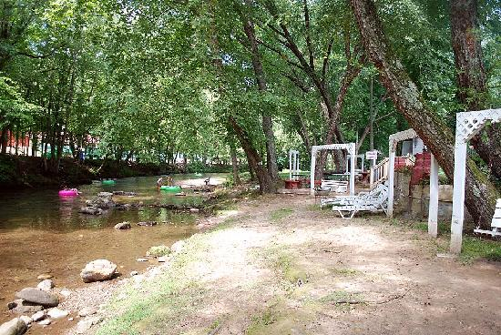 Riverbend Motel & Cabins: The river frontage at the hotel with tubers and the hotel's swings.