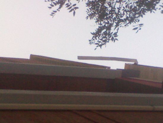 Quality Suites North / Galleria: what appears to be soffit swinging in the wind