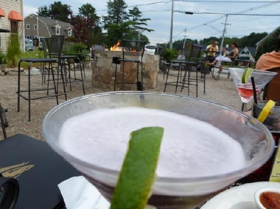 BeachFire Bar & Grille: A delicious martini with a glipse of the outdoor seating and awesome fire pit!