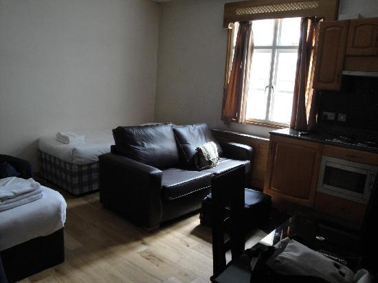 Hyde Park Suites Serviced Apartments: La vue depuis l'entrée, le lit simple à droite, le canapé, et un morceau du lit double