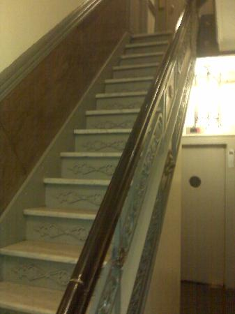 Larchmont Hotel: Stairs in entry hall with quaint, small elevator behind