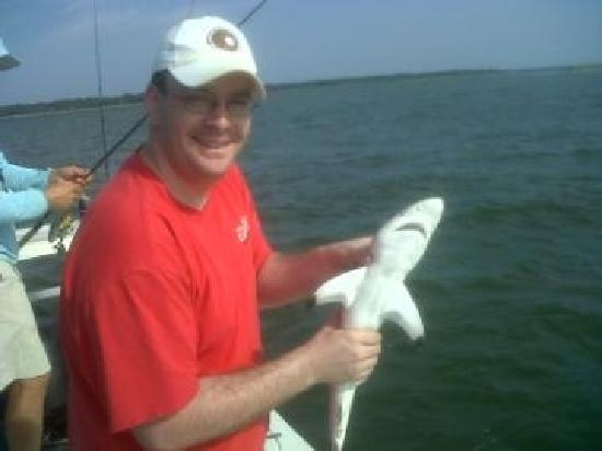 Me holding my bonnet while captain brian helps my sister for Off the hook fishing charters