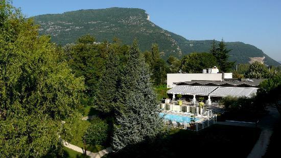 Hotel Novotel Grenoble Nord Voreppe : Jardin, piscine et terrasse vus d'une chambre.