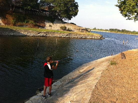 Plantation Inn Granbury: Canal where lake house is located. Son fishing.