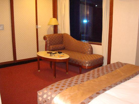YoMi Hotel: Loveseat, window facing the street, foot of the bed and bathroom sliding wall