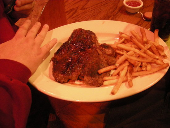OutBack : My husband's T-Bone steak. Let me state that he has really big hands!!!
