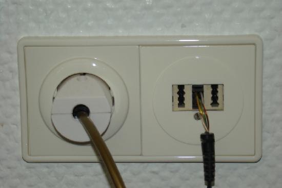 Hecker`s Hotel Berlin: Light dimmer switch connected to a socket through live wires