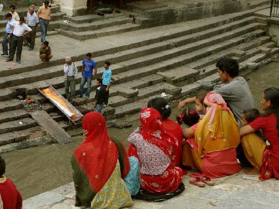 วัดปศุปฏินาถ: Angehörige beobachten die Zeremonie vom anderen Flussufer aus