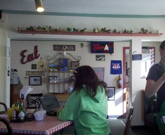 The Eatery: Another patron checks computer. Wall is near east entrance. Booths and tables available.