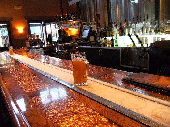 Rock Bottom Restaurant & Brwry: Eisgekühlte Abstellfläche für Bier auf dem Bartresen