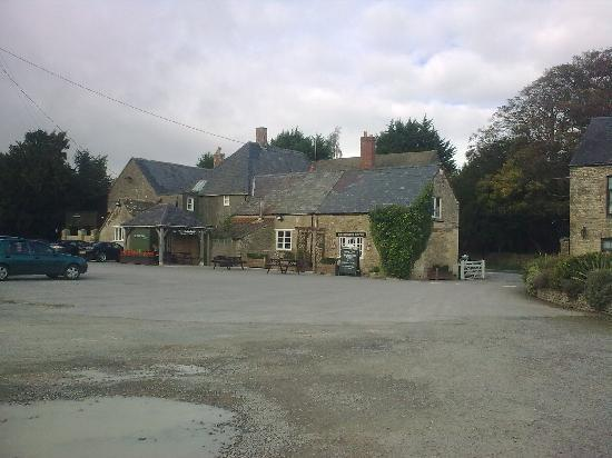 Hunter's Hall Inn: The rear of the Inn with the pot holed car park full of puddles.