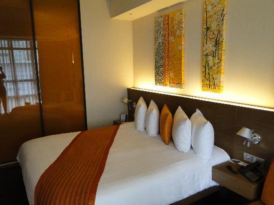 โรงแรมพูลแมน บางกอก คิงเพาเวอร์: King bed in subtle colours with sliding doors that look into the bathroom