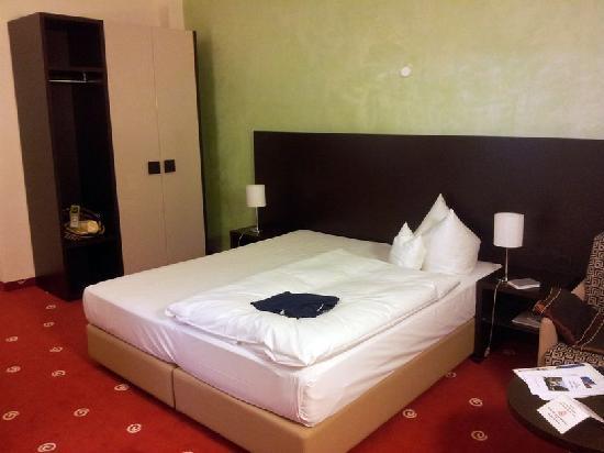 Galerie-Hotel Bad Reichenhall: Bett, dahinter Kleiderschrank mit Safe