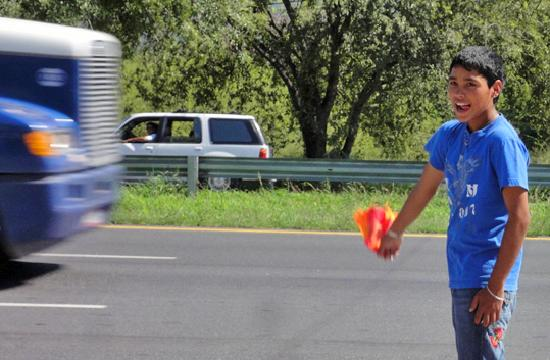 El Mexikanissimo : This young gentleman will flag you into the parking lot so you don't get run over by a big truck