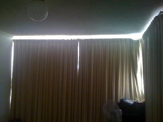 Astor Apartments Brisbane: Early morning sun light escaping into the bedroom