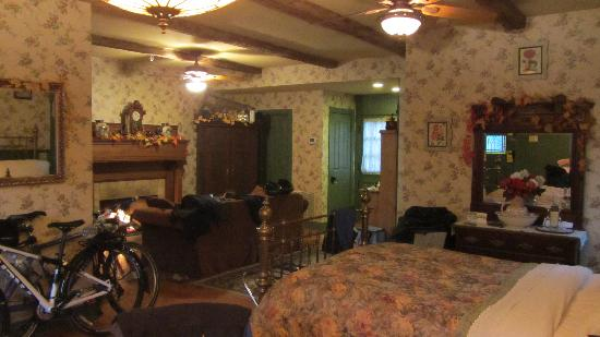 The Widow McCrea House Victorian Bed and Breakfast: queen bed, living area with fireplace & entertainment center beyond