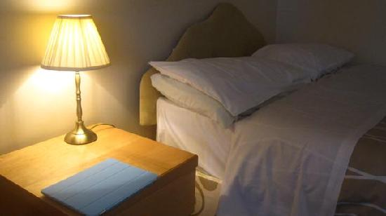Luther King House: bedside table, lamp, bed