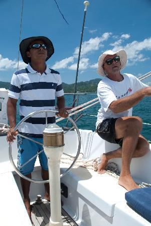 Surfari del Mar - Day Tours: Mate Bismark at the helm capitan jack trimming sails