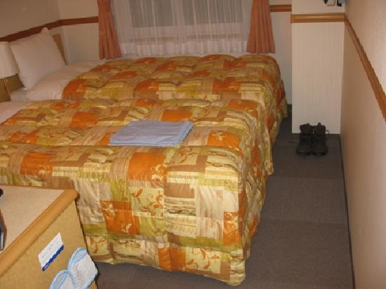 Toyoko Inn Tokyo Nihonbashi: 2 twin beds in twin room, slippers, and pressed cotton robes on bed