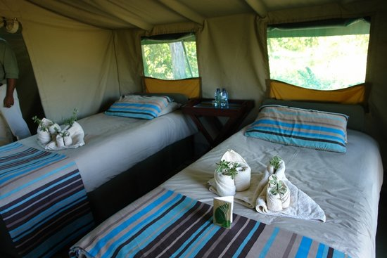 Linyanti Bush Camp: Comfortable twin beds, bedside tables, a hanging canvas wardrobe, luggage bench and sisal mattin