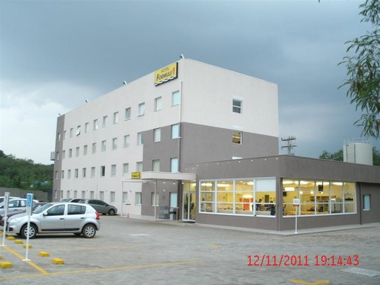 Ibis Piracicaba: O hotel e o estacionamento (a área envidraçada é a recepção e a área de café da manhã)