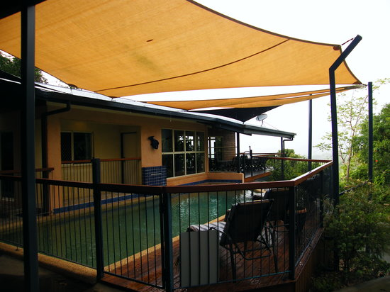 Kookas Bed & Breakfast: View of the pool deck during a tropical rainstorm