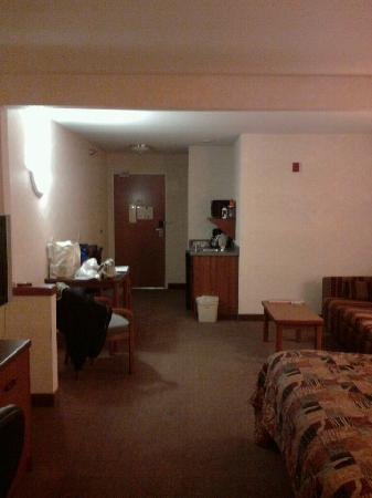 AmericInn by Wyndham Rochester Airport: View of table and 2 chairs with sink/microwave area and door.