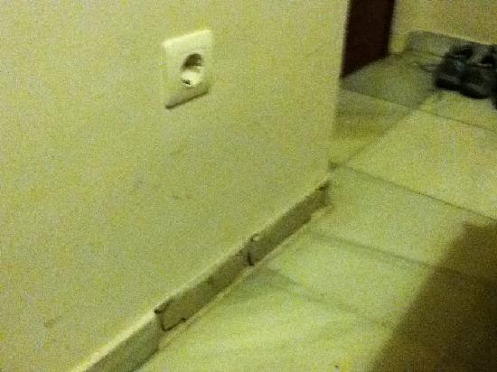 Pension Veracruz: missing tile at bottom of wall, with plaster crumbling on the floor.