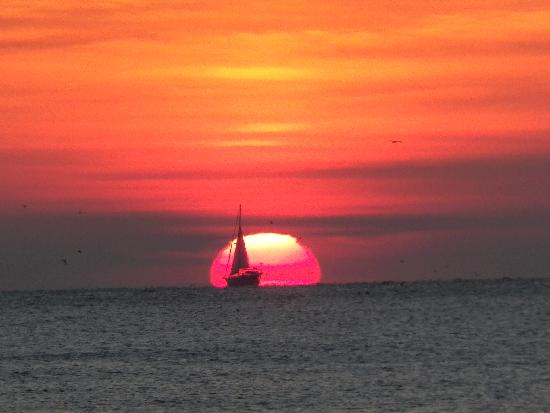 Caribe Beach Resort: Sunrise with sailboat passing by - from the Caribe