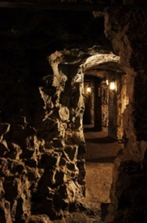Mercat Tours : Experience the underground of Edinburgh with smaller rooms leading of a main walkway.