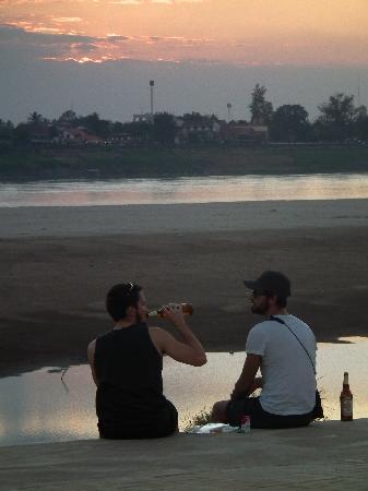 Youth Inn : ホテル前のメコン河岸で夕日を眺めながら飲むビア・ラオ