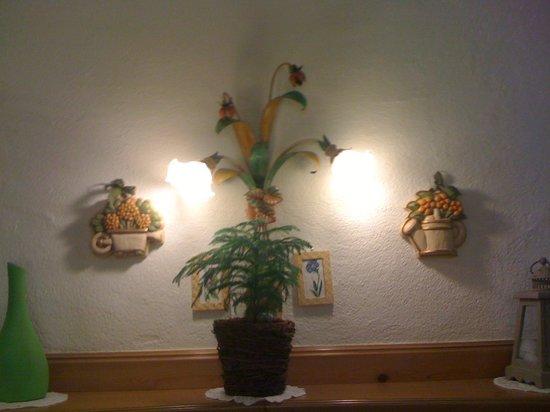 Pizzeria La Grotta: sulla parete, lampade a foglie e quadretti a punto croce