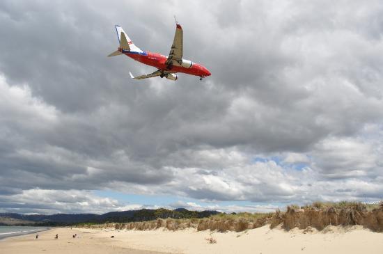 Ramada Resort Seven Mile Beach: Plane from Sydney flies over children playing on Seven Mile Beach