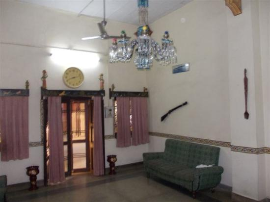 Ishwari Niwas Palace: The lounge with guns swords and paintings on the walls