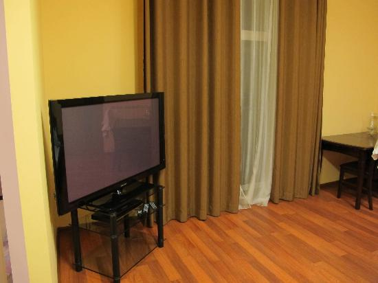 KievInn Apartment Complex: Lounge room has dining table, 2 sofas, big screen HD TV and balcony