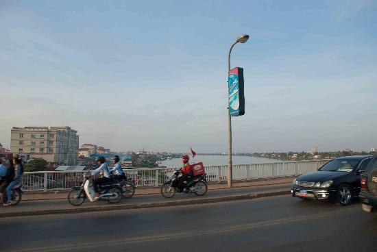 Motos riding on the footpath across the Chroy Changvar Bridge