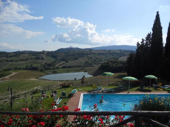 Fattoria Poggio Alloro: View of the pool, Tuscan hills, and San Gimignano from the dining area