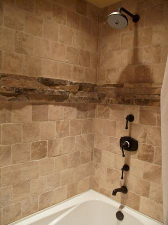 Niwot Inn & Spa: flagstone detail and rain shower head in the bath, Chimayo Suite