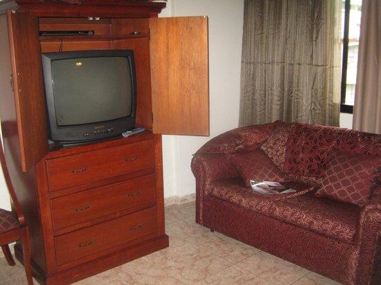 Hotel Coral Suites: Televisor y sofa para descansar.