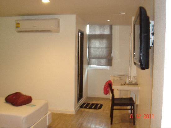 First House Bangkok: Towards the toilet. No wardrobe, just a fridge, small table, small window and flat screen tv