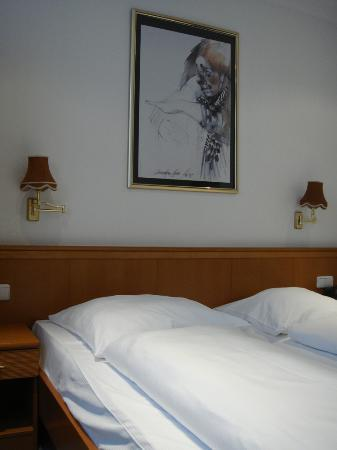 Panorama Am Adenauerplatz Hotel: Bed, with side tables and lamps; somewhat creepy clown art as decoration.