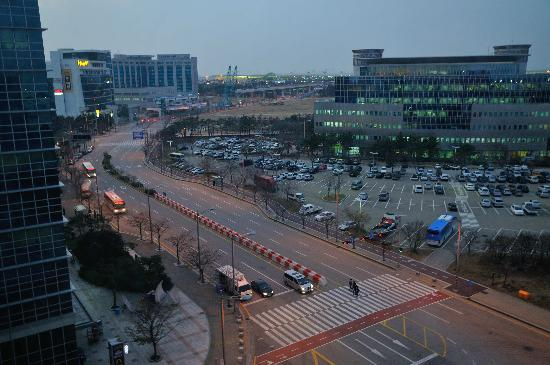 Global Guest House: View from the room - the shuttle bus stop to the airport is adjacent to the car park