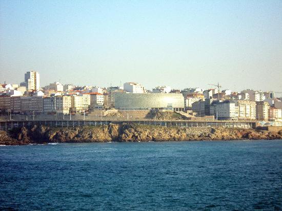 El Domus en el centro de la foto. Es el edificio de pared brillante y tono verdoso.
