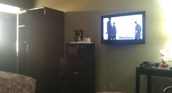 Super 8 Chandler Phoenix : TV, coffee maker, microwave, fridge with a freezer, and closet.