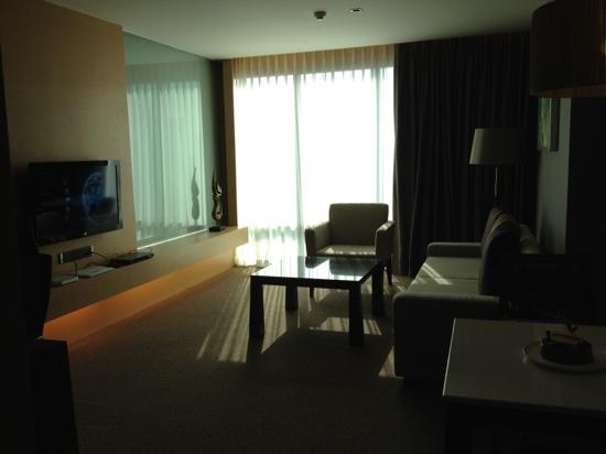 Sivatel Bangkok: Living room of suite. there is a glass wall separating bedroom from living room