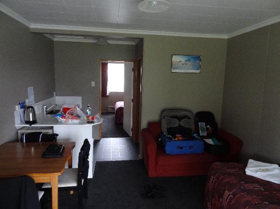 High Country Holiday Lodge: Blick ins Zimmer. Hinten das Schlafzimmer, im Rücken die Terasse und das Auto.