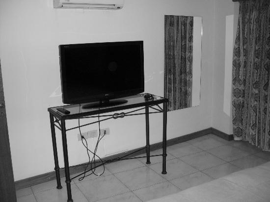 Garden All Suites: TV... O AR condicionado fica sobre a TV de frente para a cama
