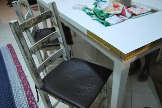 Solar dos Girassois: Sillas viejas y sucias, y mesa deteriorada.