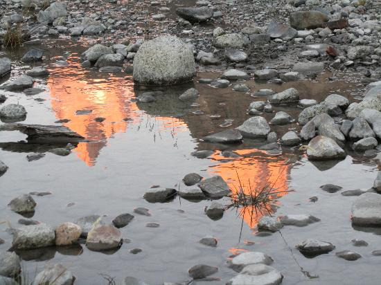 Hosteria El Pilar: Sun rise on the mountain, as seen in a puddle near the hotel